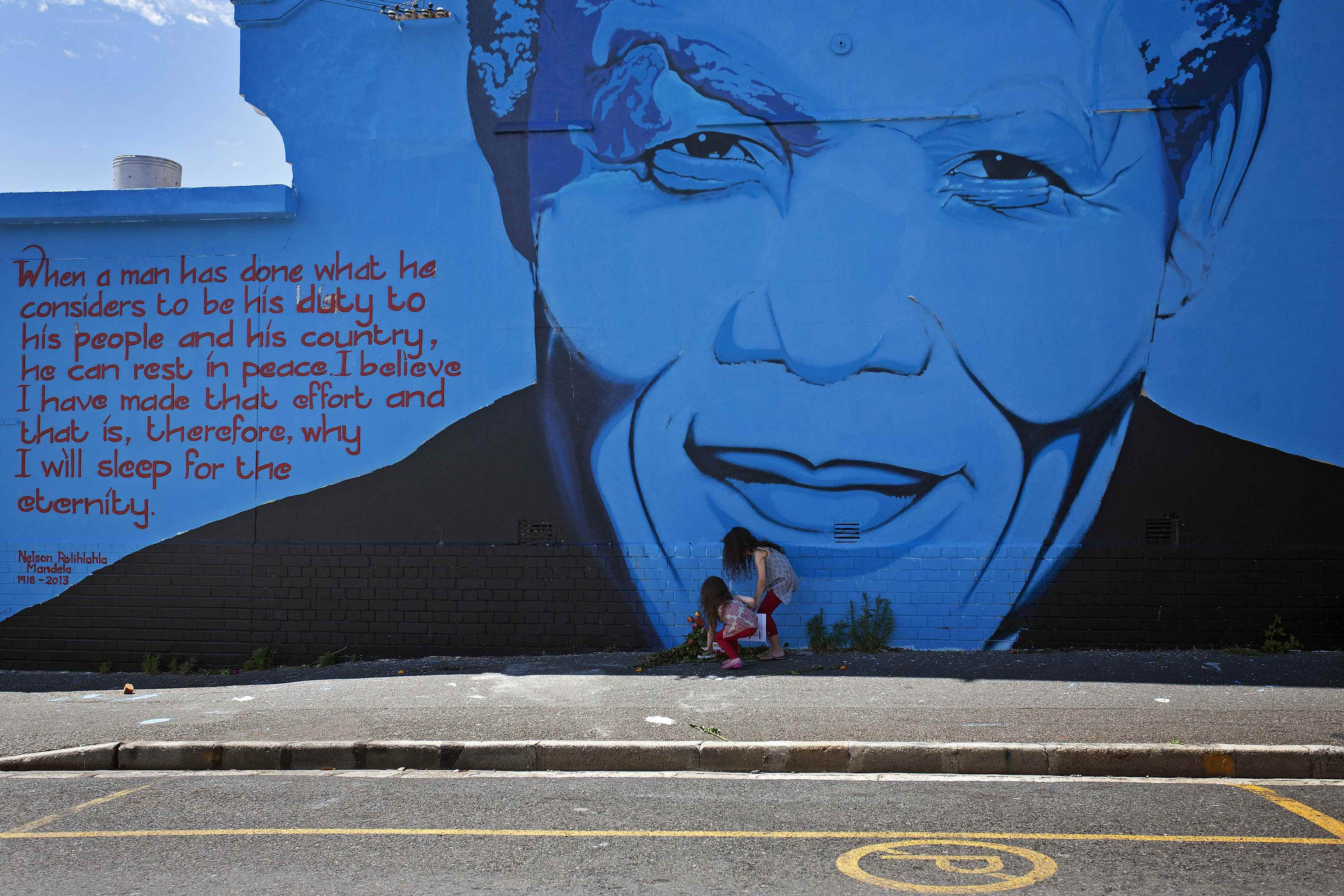 Kitty Harris, age five, and her sister India, eight, lay bouquets of flowers for the late former South African President Nelson Mandela at a wall mural in Cape Town